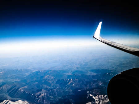 View from plane window on Alps, plane wing and enginie. Travel and transport concept. Copy space. 版權商用圖片