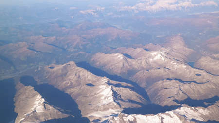 Alps, view of the mountains from the window of the plane. Land bending and nature concept.