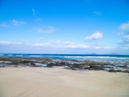Beach and Atlantic Ocean in Caleta de Famara, Lanzarote Canary Islands. Beach in Caleta de Famara is very popular among surfers. Copy space. 版權商用圖片