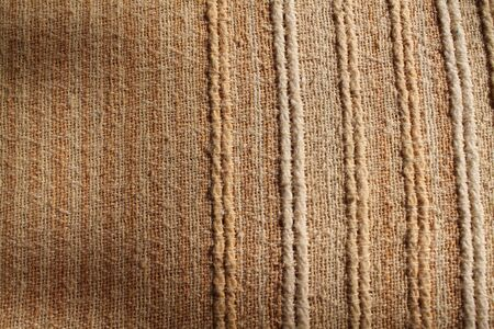 Silk fabric wallpaper texture background in sepia pastel yellow creme beige color tone: Fine natural raw Thai silk detail textured organic fiber textile backdrop earth brown toned colour Stock Photo