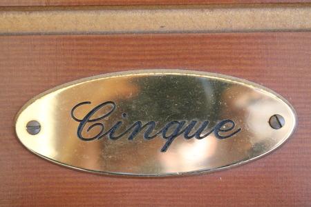 House number 5 sign (writen in italy language) on brown painted wooden door Standard-Bild