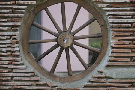 Tile wall with wheel on the wagon. Stock Photo