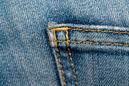 Closeup of obsolete blue jeans pocket Denim texture, macro background for web site or mobile devices Standard-Bild - 92215784