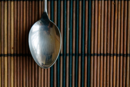 Metal vintage spoon on a wooden bamboo table