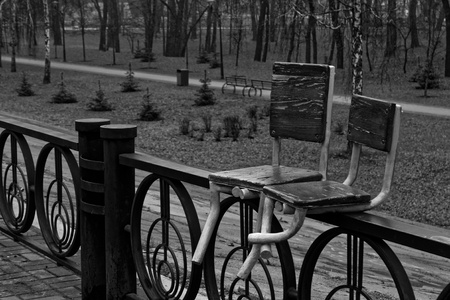 Abandoned chairs welded to steel iron fence, abstract background, monochrome image