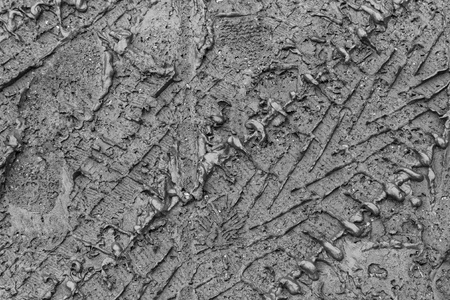 Mud texture or wet black soil as natural organic clay and geological sediment mixture as in roughing it in a dirty muddy country road bog after the rain or rainy season found in a damp moist climate.