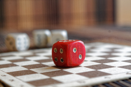 Stack of three white plastic dices and one red dice on brown wooden board background. Six sides cube with black dots. Number 4, 2 Stock Photo