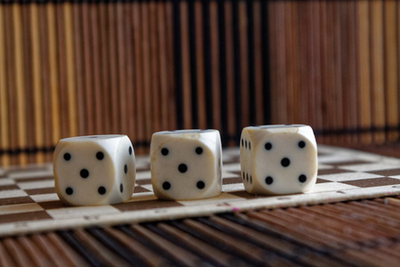 Stack of three white plastic dices on brown wooden board background. Six sides cube with black dots. Number 5