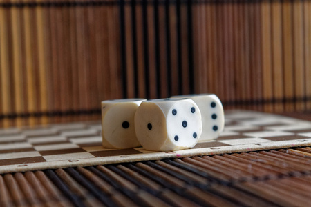 Stack of three white plastic dices on brown wooden board background. Six sides cube with black dots. Rundom number Stock Photo