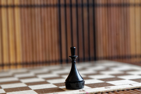 Wooden chess Board and plastic chess queen, on board Stock Photo