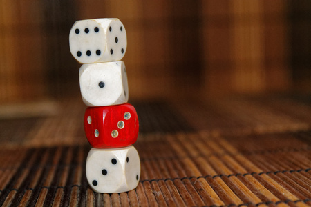 Stack of three white plastic dices and one red dice on brown wooden board background. Six sides cube with black dots. Number 1, 3, 6 Stock Photo