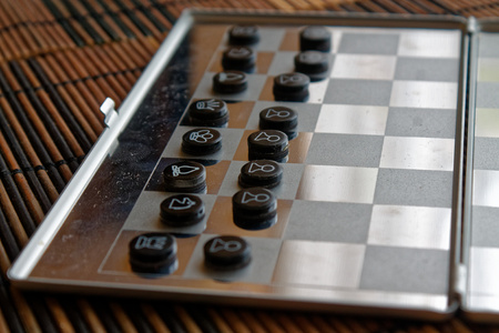 Photo with a picture of a chess steel Board and chess pieces, Metal chess pieces on a chess Board with reflection 写真素材