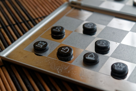 Photo with a picture of a chess steel Board and chess pieces, Metal chess pieces on a chess Board with reflection Stock Photo