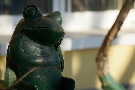 Steel green frog sits in crossed legs gesture on stone stairs. Garden statue Selective focus on the face of frog