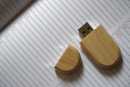 Usb flash drive with wooden surface on note page for USB port plug-in computer laptop for transfer data and backup business concept.