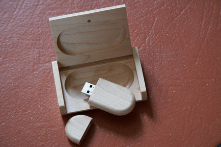Usb flash drive with wooden surface in wooden box on desk for USB port plug-in computer laptop for transfer data and backup business concept. Imagens