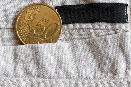 Euro coin with a denomination of 50 euro cents in the pocket of linen pants with black stripe 免版税图像
