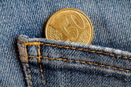 Euro coin with a denomination of fifty euro cents in the pocket of blue worn denim jeans