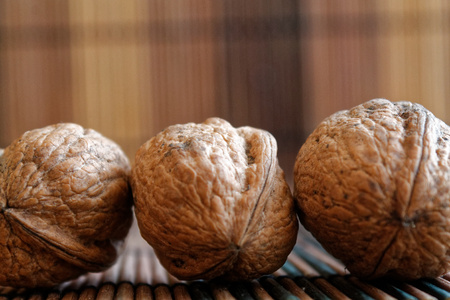 Three walnuts lie on a wooden bamboo table, background for web site or mobile devices. Stock Photo