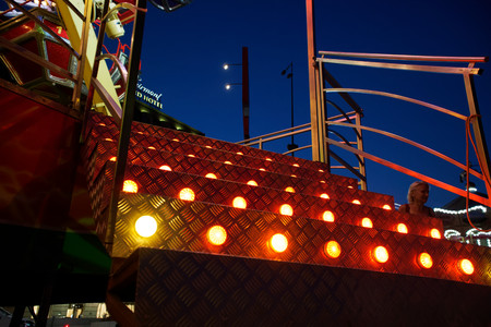 Staircase to Ferris wheel attraction illuminated with colorful lights