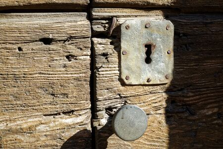 Rustic door knob and keyhole on the old wooden door, Vintage style