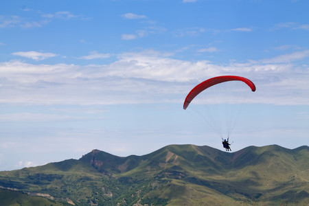Mountain parasailing, Skydiving flying over the mountains. parachute extreme sport.