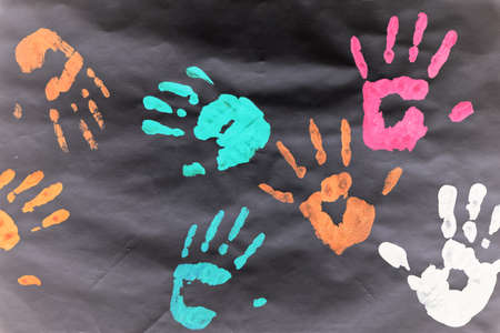 Color prints of kid's hands on a white sheet.