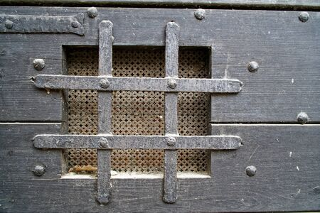Medieval window in door with iron grid for safety