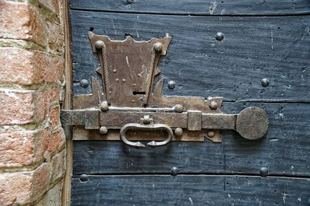 Old wooden door with metal knob and rusty medieval bolt