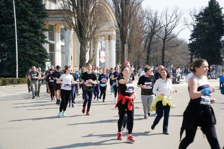 Kyiv - Ukraine, April 07, 2019: Crowd of People and Athletes Runners Run along the Road in the City. City Marathon Race. Racers starting to run on the marathon day.