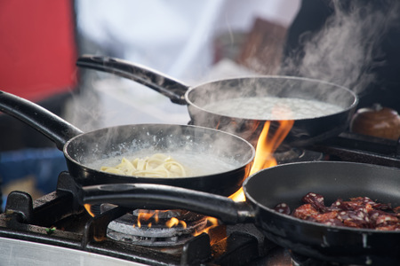 Poêle à frire en feu, chef Faire frire les légumes en feu les jeter dans une poêle à frire Banque d'images