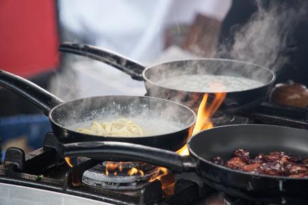 Sartén en llamas, chef Freír verduras al fuego tirándolas en una sartén Foto de archivo