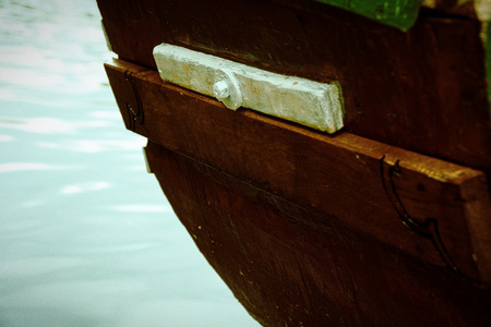 Old wooden boat stern on river and fountain behind.