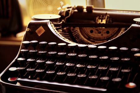 Old typewriter in antique photography vintage simulated, grunge photo. Imagens