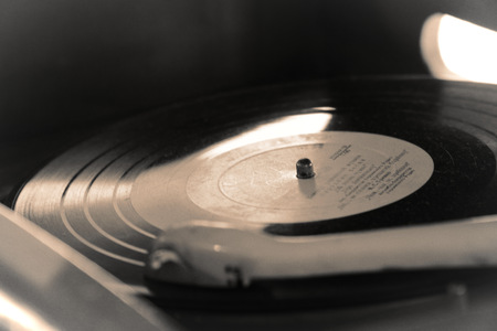Turntable, Old record player stylus on a rotating disc, vintage filtered, selective focus.