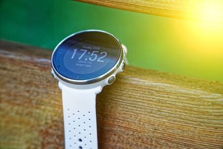 Sport watch for running white color on wooden bench. Fitness watch for tracking daily activity and power training