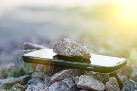 Cell phone with broken glass on gravel granite stones, unbreakable gadget, sun beam lights.