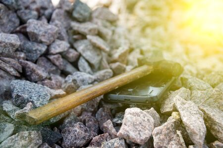 Broken glass of smartphone with hammer on gravel stones. Selective focus and sun beam lights. 写真素材