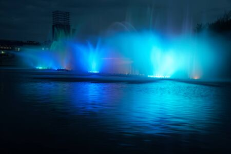 Colorful water fountains with laser and light reflection over lake.