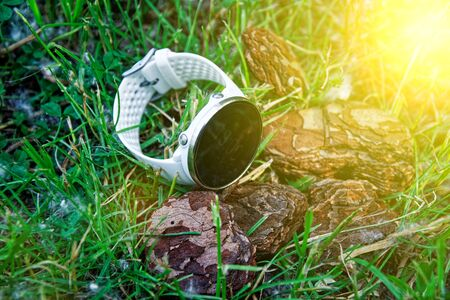 Sport watch for running white color on the ground in the grass. Fitness watch for tracking daily activity and strength training