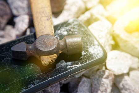 Broken glass of smartphone with hammer on gravel stones. Selective focus and sun beam lights. Reklamní fotografie