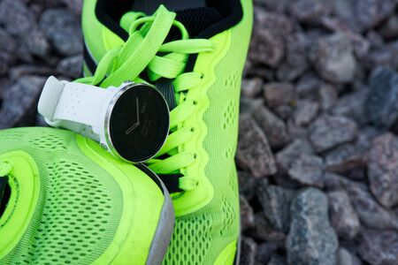 Sport watch for crossfit and triathlon on the green running shoes. Smart watch for tracking daily activity and strength training