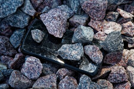 Cell phone with broken glass on gravel granite stones, unbreakable gadget. Stock Photo