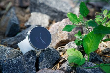 Sport watch for triathlon on the granite gravel. Smart watch for tracking daily activity and strength training