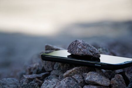 Cell phone with broken glass on gravel granite stones, unbreakable gadget.