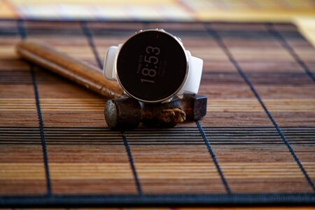 Sport watch in white color on wooden table, Smart watch for running and fitness training. Hammer with wooden handle on background.