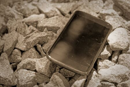 Broken cellphone abandoned and lost among the gravel. Reklamní fotografie