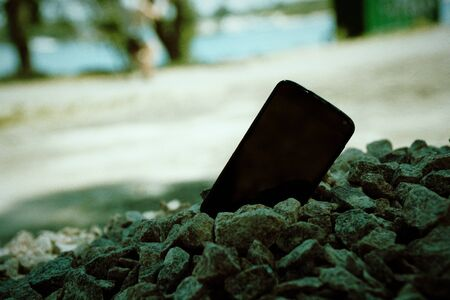 Broken cellphone abandoned and lost among the gravel.