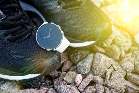Sport watch for crossfit and triathlon on the running shoes. Smart watch for tracking daily activity and strength training. Sun beam lights