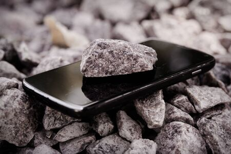 Cell phone with broken glass on gravel granite stones, unbreakable gadget. Reklamní fotografie